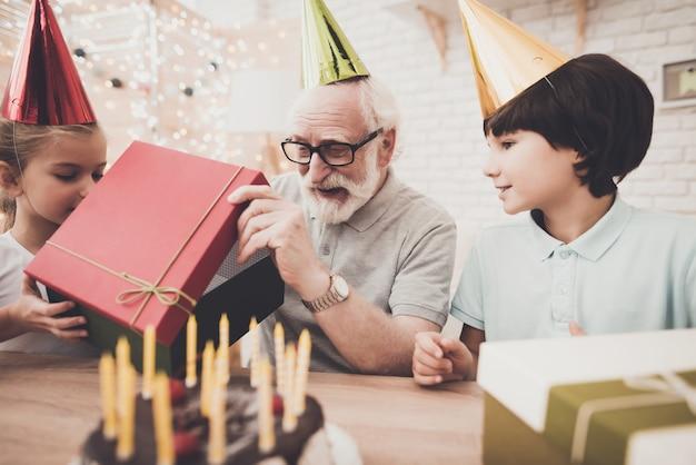 O avô feliz da festa de anos abre a caixa de presente.