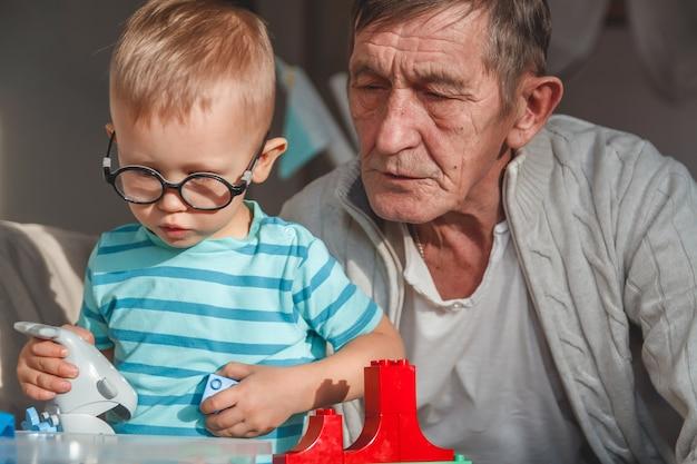 O avô idoso brinca com o neto com blocos de plástico