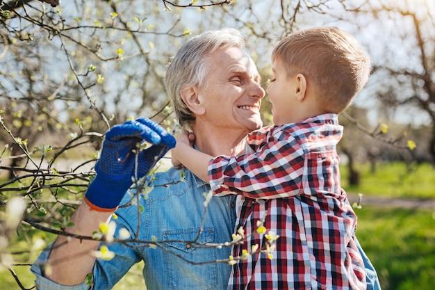 O avô radiante com um sorriso largo enquanto segura o neto e passa um dia cuidando do jardim juntos