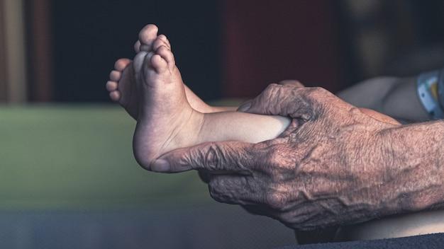 O avô segura as perninhas do neto
