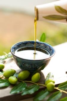 O azeite no copo. ramo de uma oliveira com azeitonas frescas. azeitonas verdes. no jardim. em uma placa de madeira. um jarro de óleo. clássicos italianos. azeitonas da itália. comida da itália