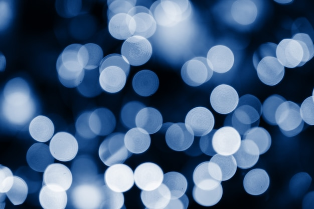 O azul abstrato circunda o bokeh para o natal de algum fundo, defocused. as luzes borradas e brilhantes coloridas suaves tonificaram a cor azul clássica na moda do ano 2020