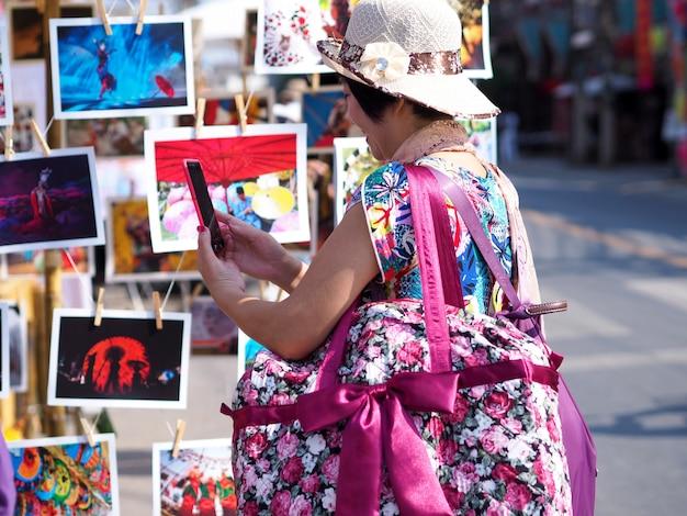 O backpacker asiático das mulheres que procura está vendo fotos das atrações turísticas no festival do turismo de tailândia.