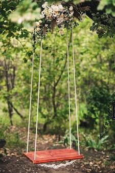 O balanço da corda pendurado em um carvalho, decorado com flores.