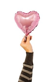 O balão de ar cor-de-rosa guardou por uma mão no isolado.
