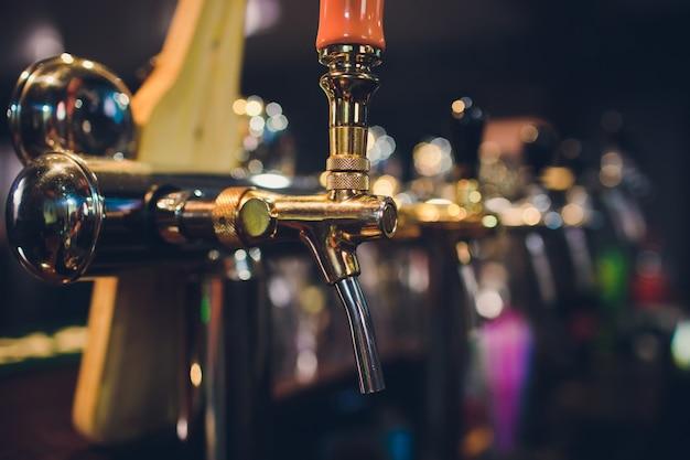 O balcão do bar com garrafas e aparelhos para distribuição de cerveja. aparelho para distribuição de cerveja no bar. bar. o bar do restaurante. aparelho para distribuição de cerveja em um restaurante.