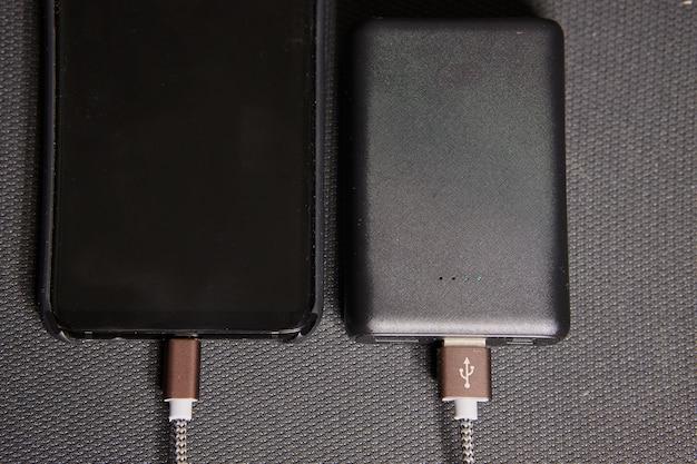 O banco de energia carrega o smartphone em um fundo preto