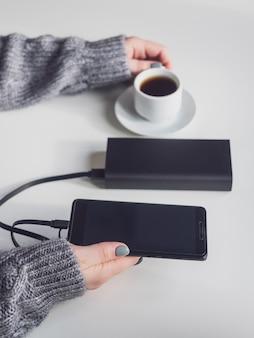 O banco de energia e o telefone são pretos. power bank carrega o telefone sobre a mesa.