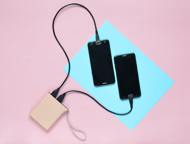 O banco de potência cobrou dois smartphones em uma superfície pastel colorida. aparelhos modernos. vista do topo. minimalismo