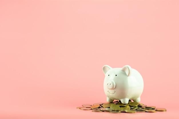 O banco piggy e uma pilha dourada das moedas no fundo cor-de-rosa. - salvar e conceito de gestão.
