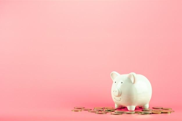 O banco piggy e uma pilha dourada das moedas no fundo cor-de-rosa.
