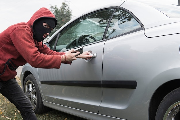 O bandido mascarado abre a fechadura central de um carro moderno caro com a ajuda de um telefone celular. conecte-se ao mirrorlink.