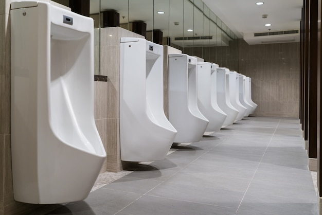 O banheiro do homem com linha de mictórios de cerâmica branca moderna no banheiro público