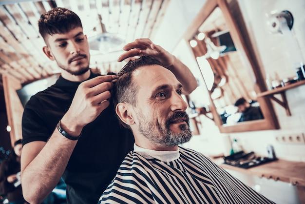 O barbeiro barbeia o homem de sorriso considerável com lâmina.