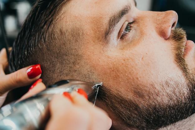 O barbeiro corta a barba para um homem brutal no salão