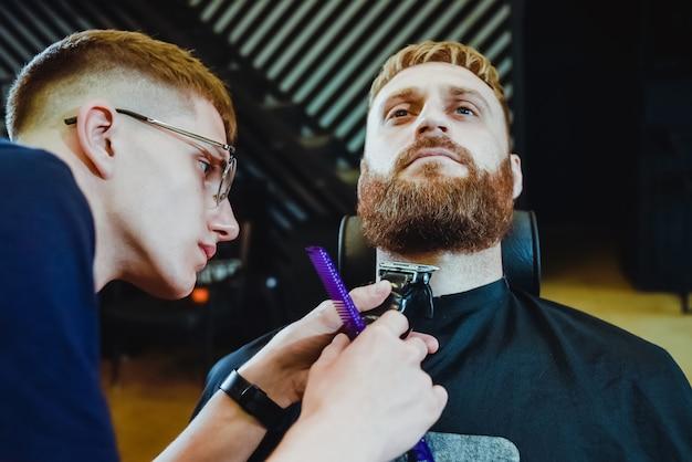 O barbeiro corta a barba para um homem no salão