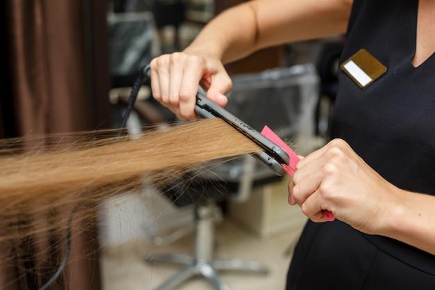 O barbeiro corta o cabelo do cliente.