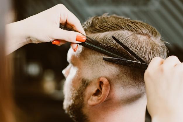 O barbeiro corta um homem barbudo com uma tesoura no salão