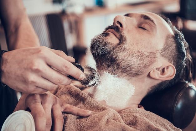 O barbeiro está escovando a espuma de rapagem na cara do homem.