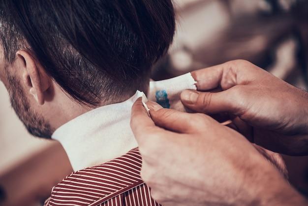 O barbeiro está gravando a nuca dos clientes antes de cortar o cabelo.