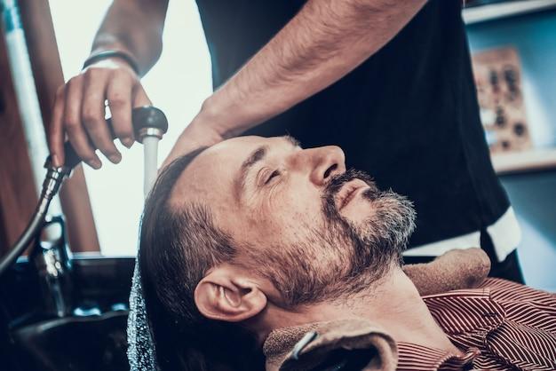 O barbeiro está lavando clientes cabelo preto da torneira.