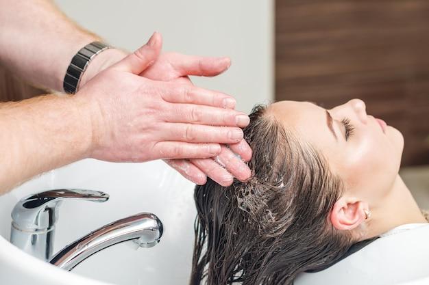 O barbeiro está lavando o cabelo da mulher na pia antes de cortar na barbearia.