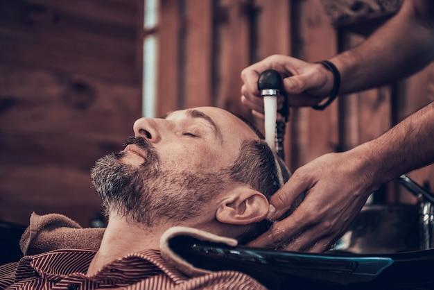 O barbeiro está lavando o cabelo preto do cliente da torneira