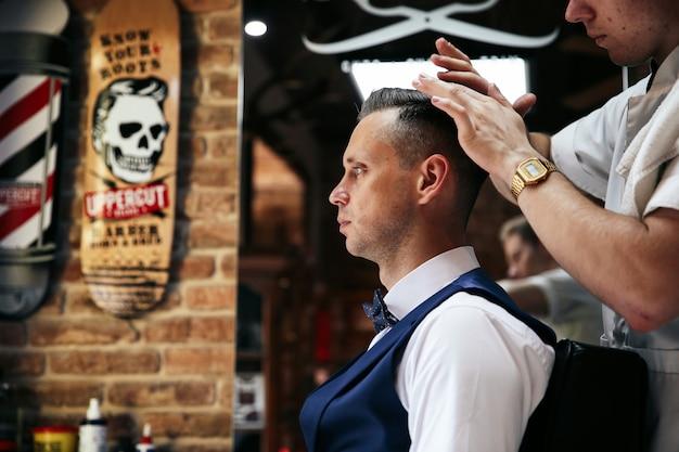 O barbeiro masculino está servindo o cliente que faz o cabeleireiro