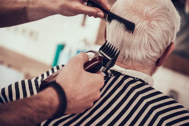 O barbeiro raspa a nuca adulta de cabelo cinzenta com lâmina