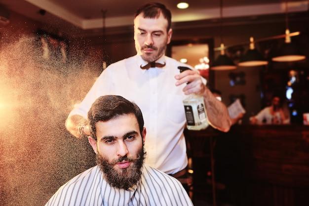 O barbeiro salpica o cabelo de um cliente jovem de uma barbearia com água de uma lâmpada.