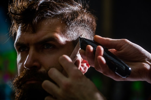 O barbeiro trabalha com o aparador de cabelo. cliente hipster cortando cabelo. mãos de barbeiro com máquina de cortar cabelo. conceito de corte de cabelo. cliente hipster cortando cabelo. homem visitando cabeleireiro na barbearia.