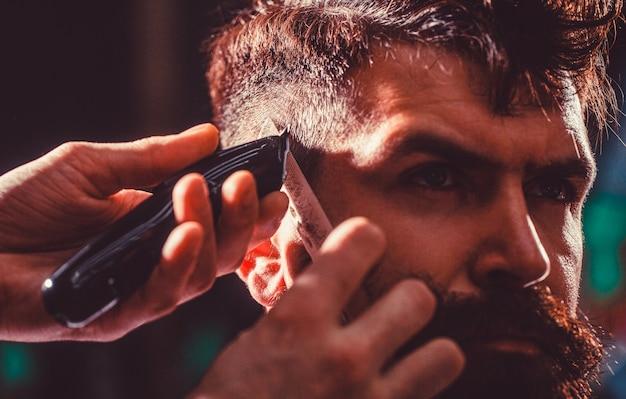 O barbeiro trabalha com o aparador de cabelo. cliente hipster cortando cabelo. mãos do barbeiro com a máquina de cortar cabelo, close-up. homem barbudo na barbearia. conceito de corte de cabelo. homem visitando cabeleireiro na barbearia.