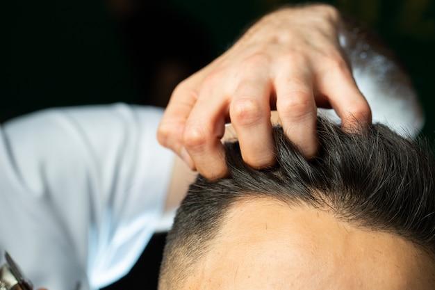 O barbeiro verifica com cabelos dos dedos