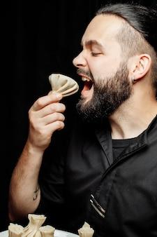 O barbudo está comendo khinkali emocionalmente