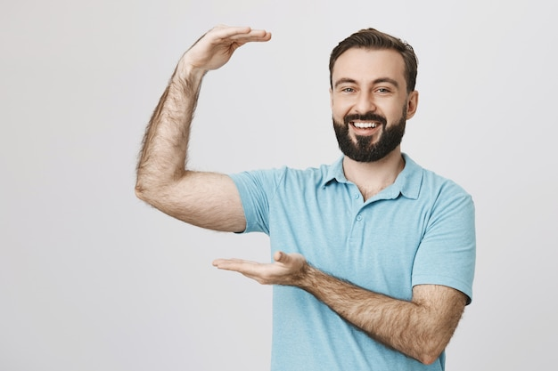 O barbudo feliz promove um objeto grande, algo grande