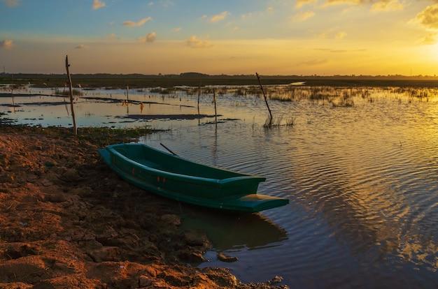 O barco de madeira e pôr do sol
