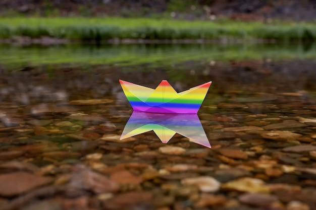 O barco de papel solitário com a bandeira do orgulho lgbt arco-íris a bordo está flutuando no rio.
