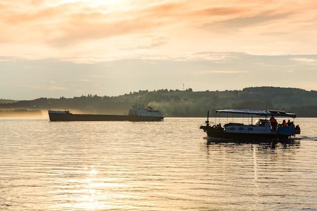O barco de passageiros e uma barcaça de carga flutuam em um rio largo à luz da noite