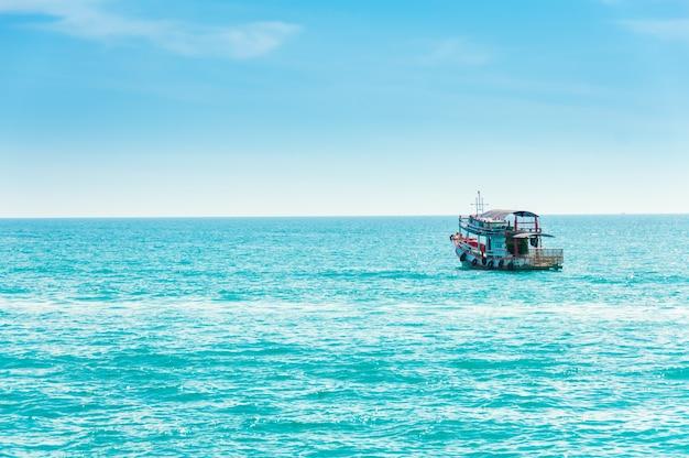 O barco de pesca navega no mar, que tem água limpa e limpa