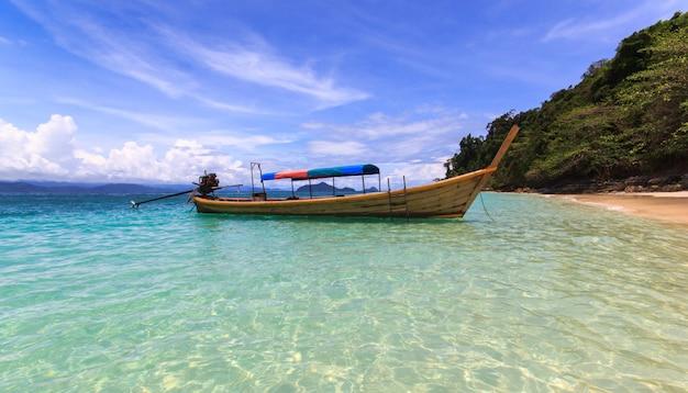O barco do pescador flutua no mar azul com a praia branca da areia e o céu azul bonito. ilha kangkao.