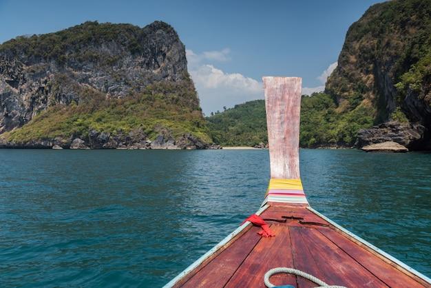 O barco longtail principal de madeira tailandês dirige-se para
