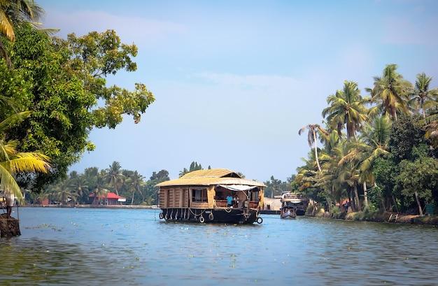 O barco navega entre palmas ao longo dos remansos em alleppey, kerala, veneza indiana. férias exóticas no sul da índia.
