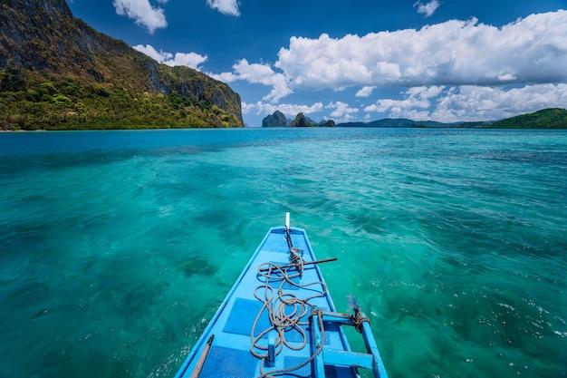 O barco paira sobre a superfície azul do oceano. arquipélago de bacuit, el nido, filipinas.