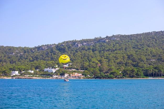 O barco puxa um pára-quedas amarelo com pessoas no mar na montanha