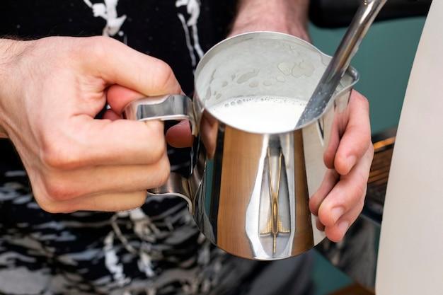 O barista bate o leite em uma jarra com o vapor de uma cafeteira