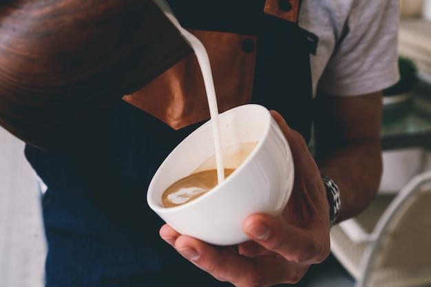 O barista de frente serve leite em uma xícara de café