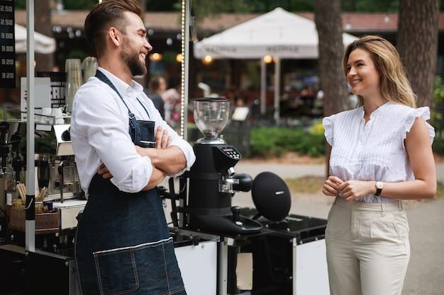 O barista e sua cliente conversam um pouco durante o dia de verão ao lado do café móvel.