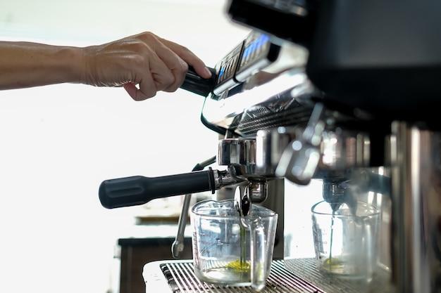 O barista está preparando bebidas na cafeteria.