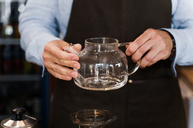 O barista gira nas mãos e olha para o bule com café antes de fazer um aeropress