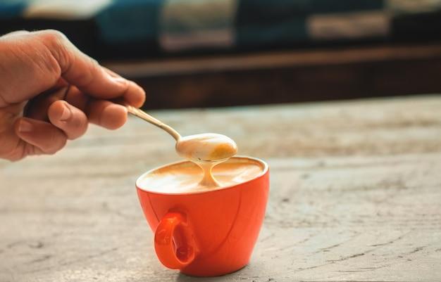 O barista mistura a espuma em um café com leite acabado de fazer em uma xícara vermelha.